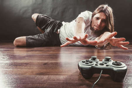 dependency: Addiction and dependency concept. Young man with pad joystick playing games.