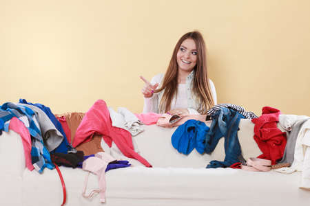messy room: Happy woman behind sofa couch in messy living room pointing at empty blank copy space. Young girl surrounded by many stack of clothes. Disorder and mess at home.