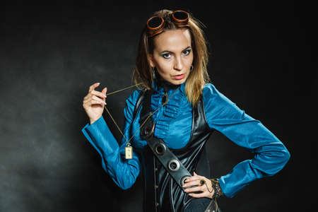 steampunk goggles: Steampunk and retro style. Attractive vintage woman with stylish accessories on dark background. Fashionable female portrait.
