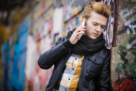 mobile communication: Technology and communication. Closeup young fashion man talking on mobile cell phone using smartphone outdoor graffiti wall background Stock Photo