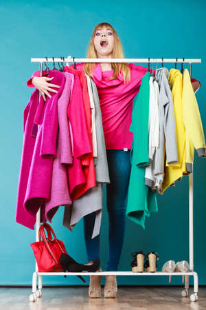grabbing: Funny woman girl taking grabbing all clothes coats and shirts in wardrobe. Young girl shopping in mall. Fashion clothing sale concept. Stock Photo