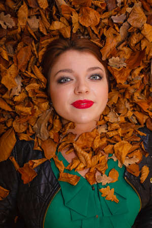 ginger hair: Nature autumn concept. Beautiful young lady is lying between leaves. Ginger hair merge with leaf colour.