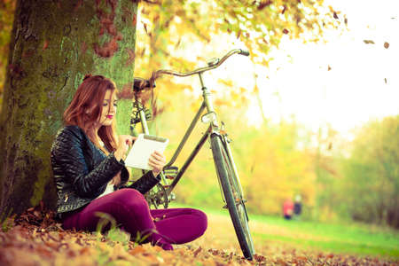 Nature, outdoors concept. Beautiful girl is sitting under the tree with her bike. Young lady is checking her tablet.