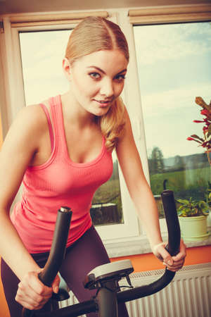 stationary bicycle: Active young woman working out on exercise bike stationary bicycle. Sporty girl training. Fitness and weight loss concept.