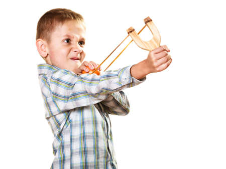 naughty boy: Children upbringing problems. Kid holding slingshot in hands. Bad naughty boy shoots from a wooden sling on white