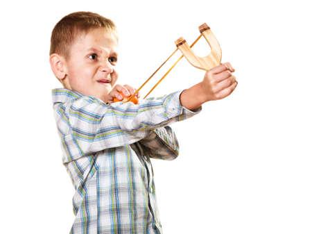 prankster: Children upbringing problems. Kid holding slingshot in hands. Bad naughty boy shoots from a wooden sling on white