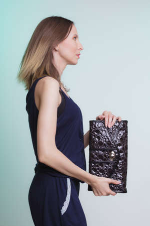 woman profile: Elegant fashionable woman with leather handbag. Stylish girl on green holding black bag. Female fashion vogue. Studio. Side profile view.