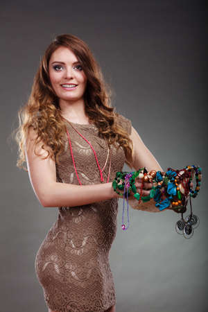 plentiful: Pretty young woman holding hat and many plentiful of precious jewelry necklaces beads. Gorgeous fashion girl. Stock Photo