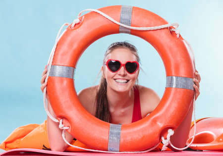 safety buoy: Happy glad young woman girl in heart shape sunglasses with ring buoy lifebuoy. Summer safety security.