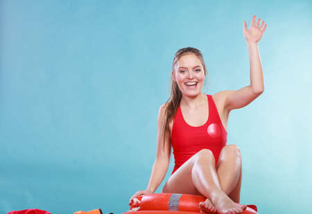 Happy lifeguard sitting on rescue tube buoy and ring lifebuoy. Joyful woman girl having fun. Accident prevention and rescue. Stock Photo