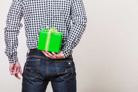 gift behind back: Man hiding green gift box with white ribbon behind back. Male hand holding christmas present. Guy wearing flannel shirt. Birthday, holiday surprise. Stock Photo