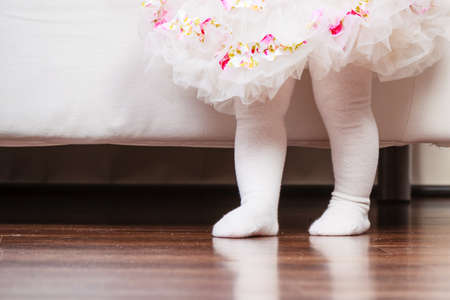 ballerina fairy: First step of baby. Part body little girl in princess fairy ballerina dress and white tights walking standing at home.