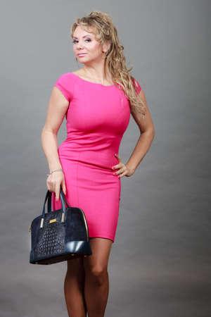 Art und Weise der Frauen. Kleidung und Accessoires. Mid blonde moderne Frau mit Handtasche im Alter. Elegante Dame im rosafarbenen Kleid mit schwarzen Tasche. Standard-Bild - 57688777