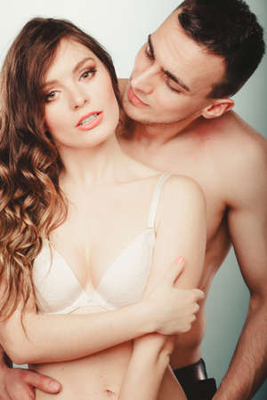 semi nude: Sexy passionate couple in studio. Handsome half naked semi nude man and pretty woman in lingerie. Love and passion. Stock Photo