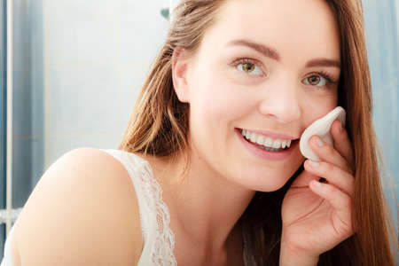 Woman removing makeup with cotton swab pad. Young girl taking care of skin. Skincare concept. Archivio Fotografico