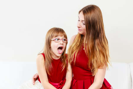 craze: Play and fun. Charming little girl making funny crazy face with joyful mother. Smiling lovely cute female child and woman. Positive facial emotion.