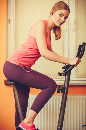 stationary bicycle: Active young woman working out on exercise bike stationary bicycle. Sporty girl training at home listening music. Fitness and weight loss concept. Stock Photo