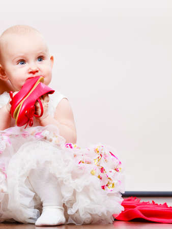 ballerina fairy: Lovely little child girl in princess fairy dress. Portrait of cute beauty sweet baby ballerina playing wit red shoes. Stock Photo