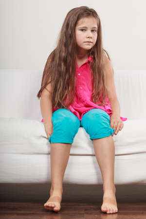 bad girl: Sad unhappy little girl kid sitting on sofa couch at home.. Lonely depressed child. Bad mood.