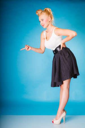 disapproving: Sexy retro girl full length. Pin up woman with blonde hairdo and shaking wagging her finger gesture sign on blue background in studio.
