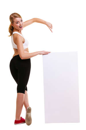 copyspace: Fitness and health lifestyle advertisement. Young woman girl holding presenting pointing blank empty banner ad copyspace isolated on white background.