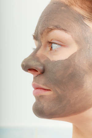 purifying: Spa beauty treatment and skin care. Closeup part of female face with clay mud facial mask.