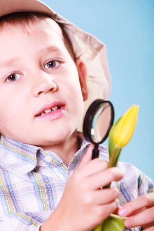 early education: Early education nature and biology. Little boy examine flower with magnifying glass.