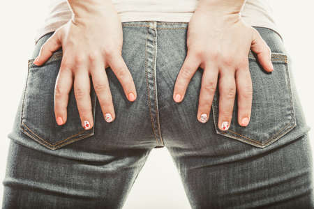 ass jeans: Closeup of human with hands palms on buttocks ass in jeans trousers.