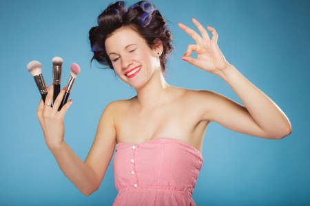 rollers: Cosmetic beauty procedures and makeover concept. Woman in hair rollers holding makeup brushes set making ok sign gesture on blue
