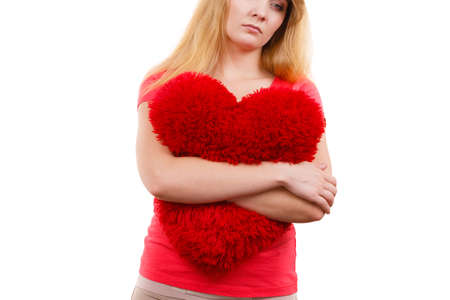 heartbroken: Woman blonde sad unhappy girl hugging red heart shaped big pillow studio shot on white. Heartbroken young female. Stock Photo