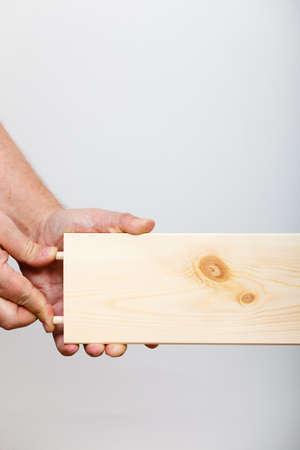 enthusiast: Human assembling wood furniture. DIY enthusiast doing home improvement.
