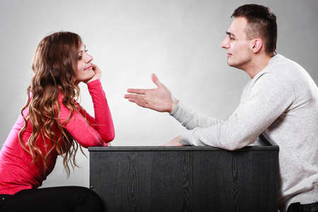 making up: Man trying to reconcile with woman. Couple making up after quarrel. Husband reaching out to wife.