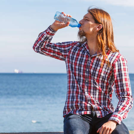 man with long hair: Man long hair wearing plaid shirt relaxing by seaside drinking water at summer sunny day
