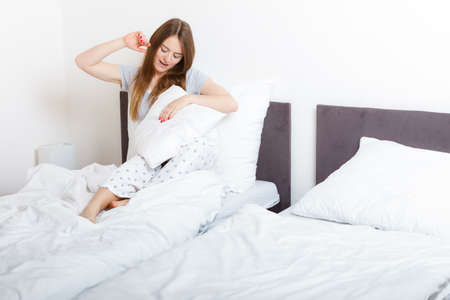 mornings: Mornings, chilling people concept. Attractive woman in the bed. Beautiful young lady has cosy pyjamas and long hair.