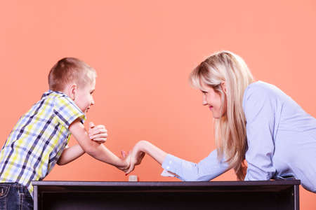 wrestle: Spending time with family fun and family bonds. Mother and son arm wrestle and have fun indoors.