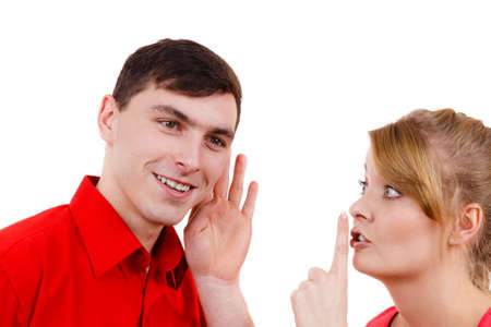 gossiping: Woman telling man some secrets, couple talking gossiping. Excited emotional girl whispering to boyfriend ear making hush gesture finger on lips