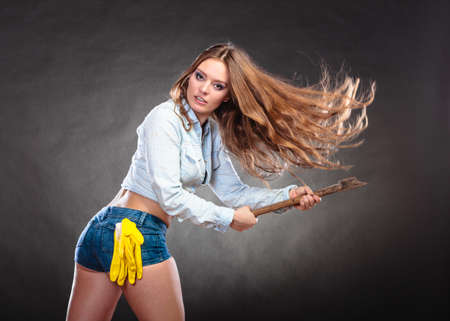 Sexy seductive woman holding axe chopper. Strong girl feminist working in man profession. Independent female. Studio shot. Stock Photo