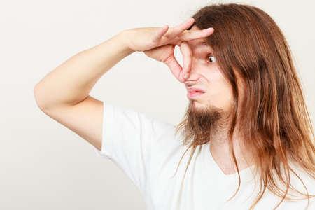 oler: Expresión de muy mal olor. larga gesto sudorosa joven de pelo toma de la mano del hombre. concepto de la sudoración.