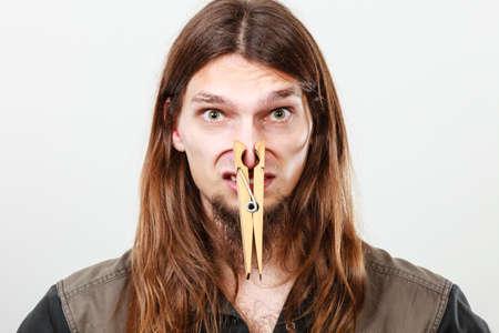 oler: Concepto de mal olor desagradable. Retrato de hombre joven de pelo largo con la nariz obstruida por el gran pinza de ropa. Foto de archivo