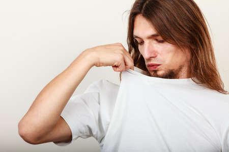 olfato: Expresión de muy mal olor. larga gesto sudorosa joven de pelo toma de la mano del hombre. concepto de la sudoración.