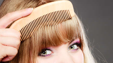 Fashion beauty and haircare concept. Closeup young woman refreshing her hairstyle girl combing her hair fringe with wooden comb Stock Photo