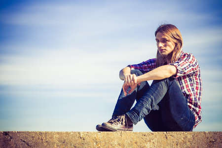 man with long hair: Man long hair wearing plaid shirt relaxing outdoor sitting on concrete wall at sunny windy day against blue sky
