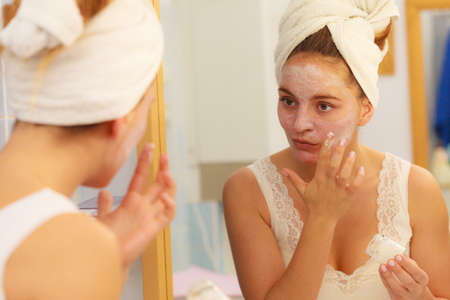 layer masks: Woman applying mask moisturizing skin cream on face looking in bathroom mirror. Girl taking care of her complexion layering moisturizer. Skincare spa treatment.
