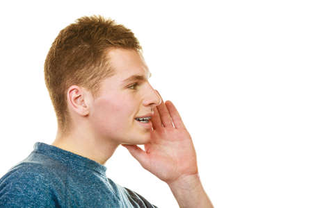 confidentially: Spread the word theme gossip. Young man face profile with hand gesture speaking, whispering isolated on white background