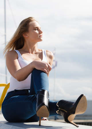 blondie: Resting and relaxation. Young beauty woman relaxing on marina on fresh air. Fashionable blondie girl spending time outdoor.