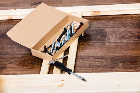 self assembly: Screwdriver and nails for furniture assembling. DIY home improvement. Stock Photo