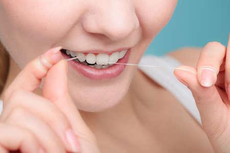 dientes sanos: La higiene bucal y el cuidado de la salud. Mujeres sonrientes Use hilo dental dientes sanos blancos. Foto de archivo