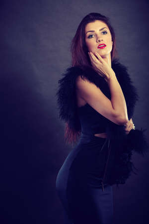 feather boa: Party celebration concept.  Magnificent long hair woman red lipstick wearing black evening dress feather boa on dark