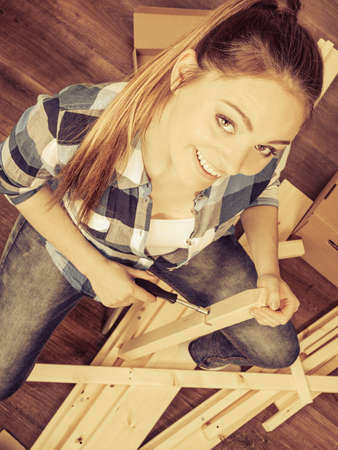 arranging chairs: Woman moving into new apartment house assembling furniture with screwdriver. Stock Photo