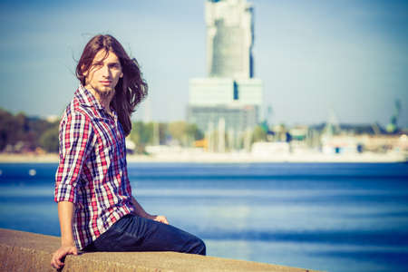 windy day: Man bearded long hair wearing plaid shirt casual style relaxing by seaside at summer sunny windy day